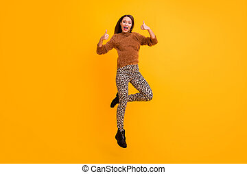 I like it. Full length photo of pretty lady jumping up high raising thumbs up approving friend youth trend look wear fluffy sweater leopard pants isolated yellow color background