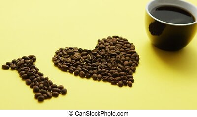 Arrangement of roasted brown coffee beans with cup of black coffee composed in phrase I love coffee on yellow surface
