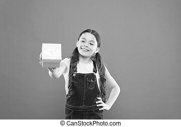 I love giving gifts. Cute small child giving a present box on orange background. Adorable little girl enjoy giving the gift. Giving and receiving, keeping it balanced