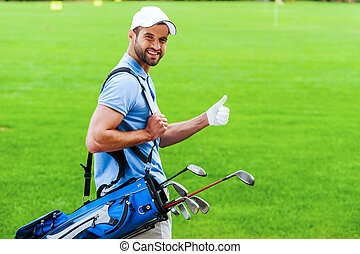 I love golfing! Rear view of young happy golfer carrying golf bag with drivers and looking over shoulder while standing on golf course