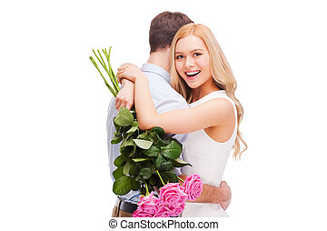 I love him so much! Beautiful young loving couple hugging while woman holding bouquet of pink roses and smiling and both standing isolated on white background