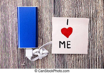 I love me heart handwritten on a note paper in different colors and heart shape in red color. Energy storage device of blue color with cable on wooden background. selfish or self love Concept.