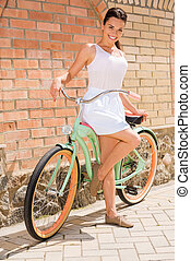 I love my bike! Full length of attractive young smiling woman standing near her vintage bicycle