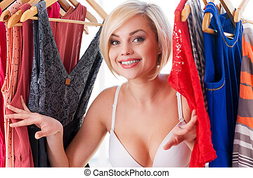 I love my clothes! Beautiful young blond hair woman looking out from the dresses in closet