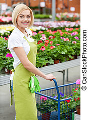 I love my job! Beautiful young woman in apron using a cart full of potted plants while standing in a greenhouse