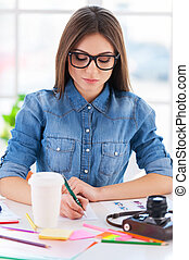 I love my job! Cheerful young businesswoman in casual wear writing something in note pad while sitting at his working place
