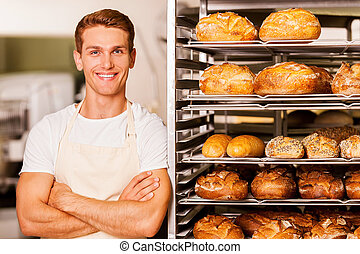 I love my job! Handsome young baker in apron keeping arms crossed and smiling while leaning at the tray with fresh baked bread
