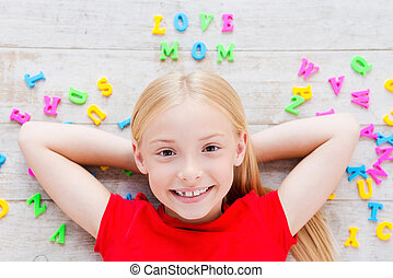I love my mom! Top view of cute little girl holding hands behind head while lying on the floor with plastic colorful letters laying around her