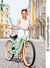 I love my vintage bicycle! Full length of attractive young smiling woman standing near her bicycle at the street