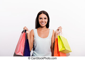I love shopping! Attractive young woman in dress carrying colorful shopping bags and smiling while standing against white background