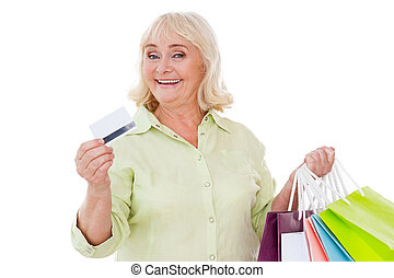 I love shopping! Happy senior woman showing her credit card and holding shopping bags while standing isolated on white background