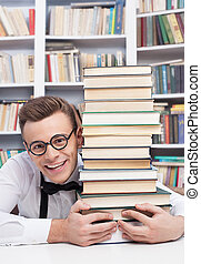 I love studying. Cheerful young man in shirt and bow tie sitting at the table in library and hugging a book stack