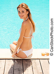I love summer! Rear view of beautiful young woman in white bikini sitting by the pool and looking over shoulder with smiling to you