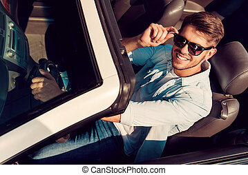 I love this car! Top view of handsome young man looking at camera and adjusting eyewear while driving his white convertible