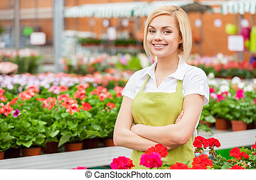 I love to work with flowers. Beautiful young woman in apron keeping arms crossed and smiling while standing in a greenhouse with flowers all around her