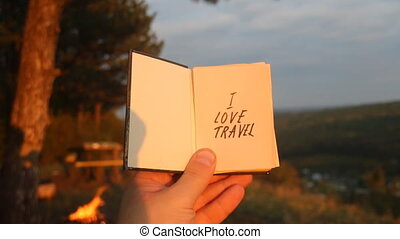 I love Travel concept. Book with with motivational inscription. Forest in the background.