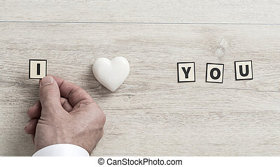 I Love You message with the hand of a man placing a letter