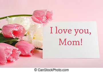 I love you Mom text on gift card in flower bouquet on pink background. Greeting card for Mom. Happy Mothers Day. Flower delivery. Congratulations card in flowers for women. Greeting card in pink tulips