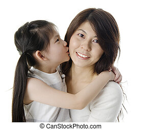 Happy Asian daughter kissing her mother on white background