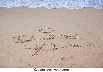 I love you on the sand near sea and waves