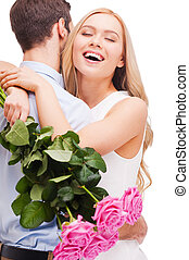 I love you so much! Beautiful young loving couple hugging while woman holding bouquet of pink roses and smiling and both standing isolated on white background