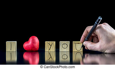 I Love You - Valentines concept with a man writing with a...