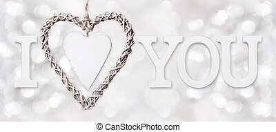 i love you text with heart of woven wood on silver blurred light background