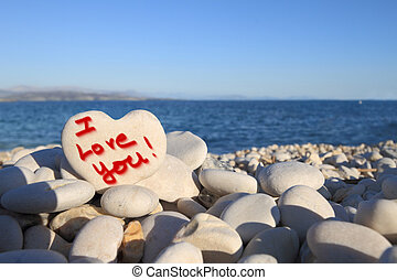 """I Love you"" written on heart shaped stone on the beach"