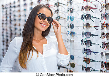 I made my choice. Beautiful young woman adjusting her sunglasses and smiling while standing in optic store