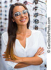 I made my choice. Beautiful young woman in sunglasses keeping arms crossed and smiling while standing in optic store