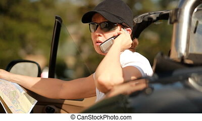 I need a GPS - A woman in a sports car looking at a map, and...