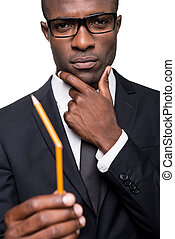 I need a new one. Thoughtful young African man in formalwear holding pencil and looking at it while holding hand on chin and standing isolated on white background