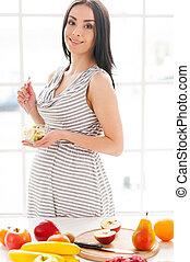 I need more vitamins at this period. Beautiful pregnant woman eating a fruit salad and looking at camera