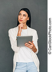 I need some inspiration online! Beautiful young pensive woman holding digital tablet and looking away while standing against grey background