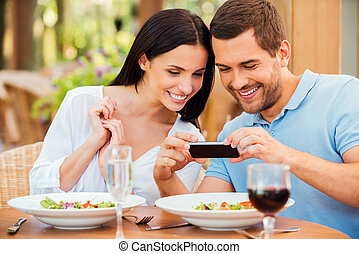 i, querer, compartilhar, este, quadro, com, friends., feliz, jovem, par amoroso, fazendo exame retratos, de, seu, alimento, e, sorrindo, enquanto, relaxante, em, ao ar livre, restaurante, junto