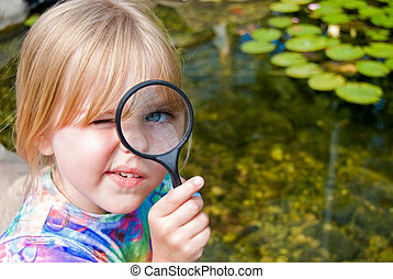 Little girl with magnifying glass.
