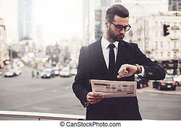 I should be there in time. Confident young man in full suit holding newspaper and looking at his watch while standing outdoors with cityscape in the background