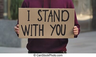 I STAND WITH YOU on a cardboard poster in the hands of male protester activist. Closeup of poster and hand. Stop Racism concept, No Racism. Rallies against racism and police brutality. The peaceful life of blacks matters. City street protest. Slow motion.