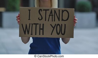 I STAND WITH YOU on a cardboard poster in the hands of white female protester activist. Closeup of poster and hand. Rallies against racism and police brutality. The peaceful life of blacks matters. City street protest. Slow motion.