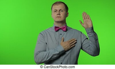 I swear! Worried honest man raising his hand up, touching chest and making sincere promise, taking oath with responsible expression. Portrait of guy posing on chroma key background. People emotions