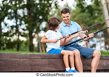 I t is all about right angle. Cheerful father and son fishing while sitting on quayside