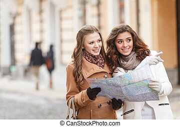 I think we should go there. Two beautiful young women holding a map and pointing away