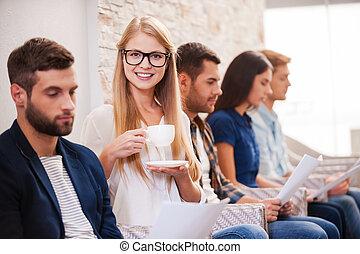 i, vontade, adquira, este, job!, grupo jovens, em, esperto casual, desgaste, sentando, uma fileira, em, a, cadeiras, e, segurando, papeis, enquanto, mulher bonita, café bebendo, e, sorrindo