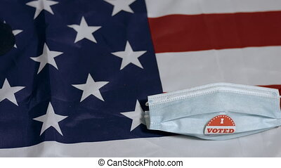 Face mask with I voted sticker falls on American flag. Usa presidential elections with Coronavirus.
