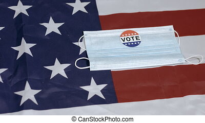 Face mask with Vote sticker falls on American flag. Usa presidential elections.