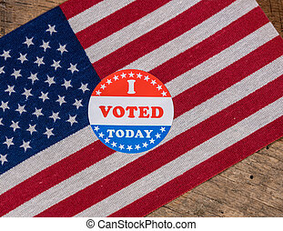 I Voted Today paper sticker on US Flag and rural wooden table