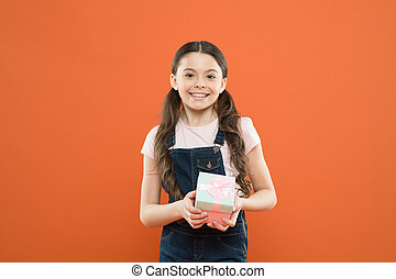 I was given such a great gift. Cute little girl holding gift box on orange background. Small child with gift pack on boxing day. Adorable kid with beautifully wrapped birthday gift box