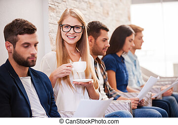 I will get this job! Group of young people in smart casual wear sitting in a row at the chairs and holding papers while beautiful woman drinking coffee and smiling