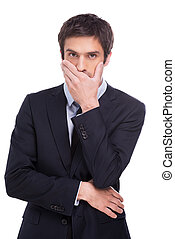 I will keep your secret. Handsome young man in formalwear covering mouth with hand and looking at camera while standing isolated on white background