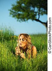 i wish -  woman blow on dandelion on green field under tree